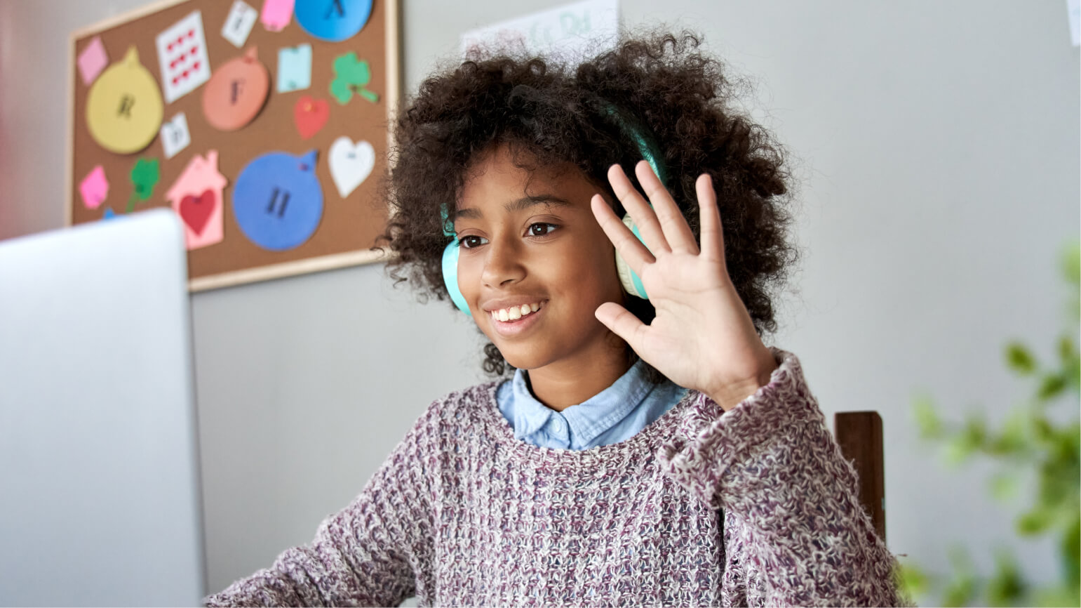 A prospective high school student waiving to the camera in a virtual private school interview.