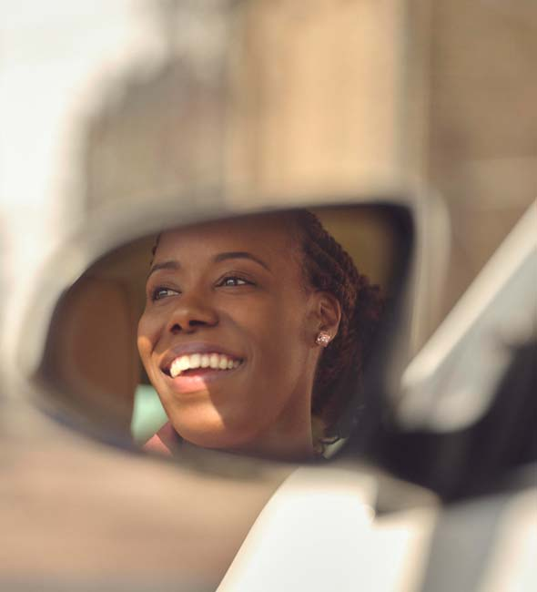 Woman smiling seen on the side mirror