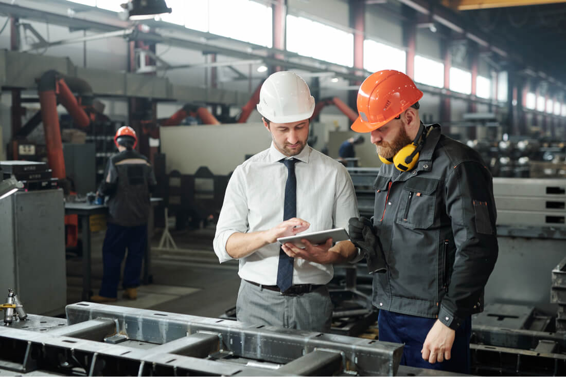 two workers checking receivables on tablet