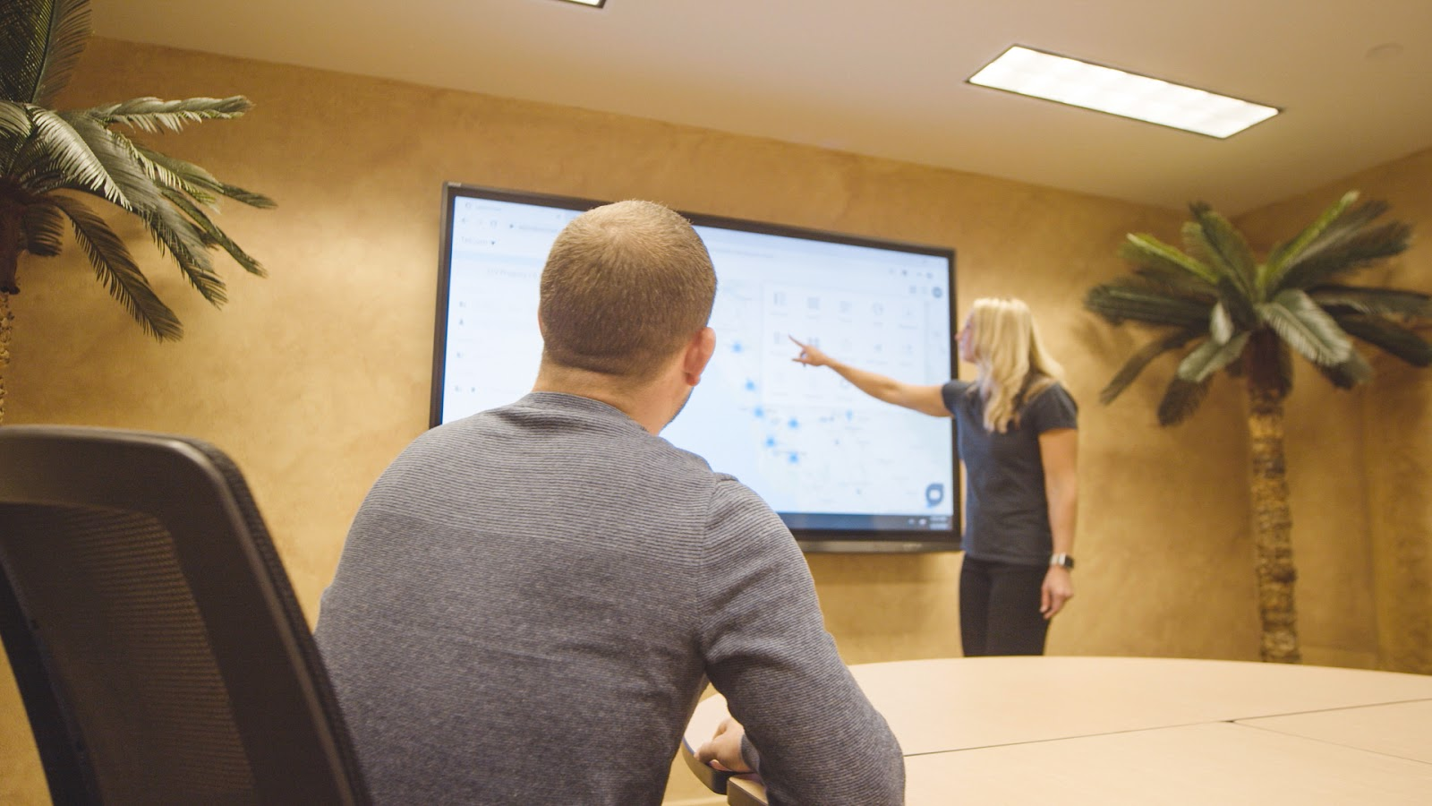 Woman demonstrates how to use a software on a touchscreen television to a man.