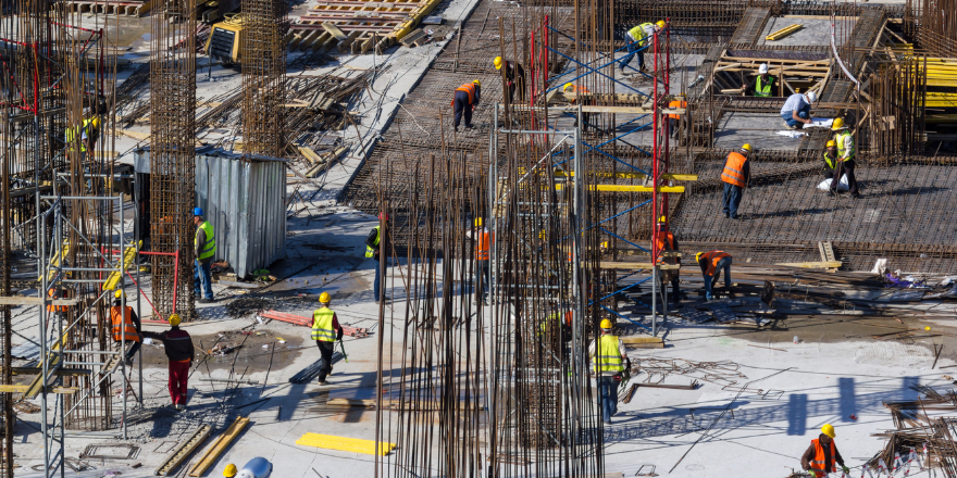 Multiple construction workers on site building with rebar.