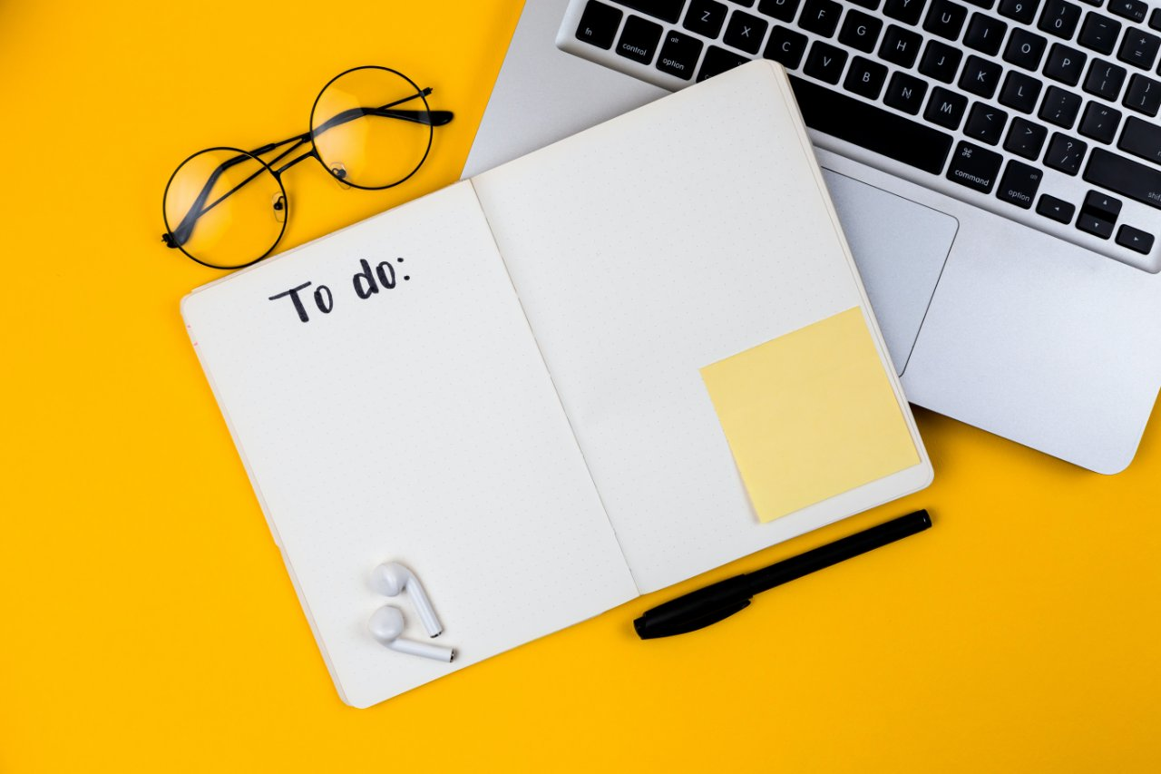 A to-do list, glasses and laptop on a yellow background.