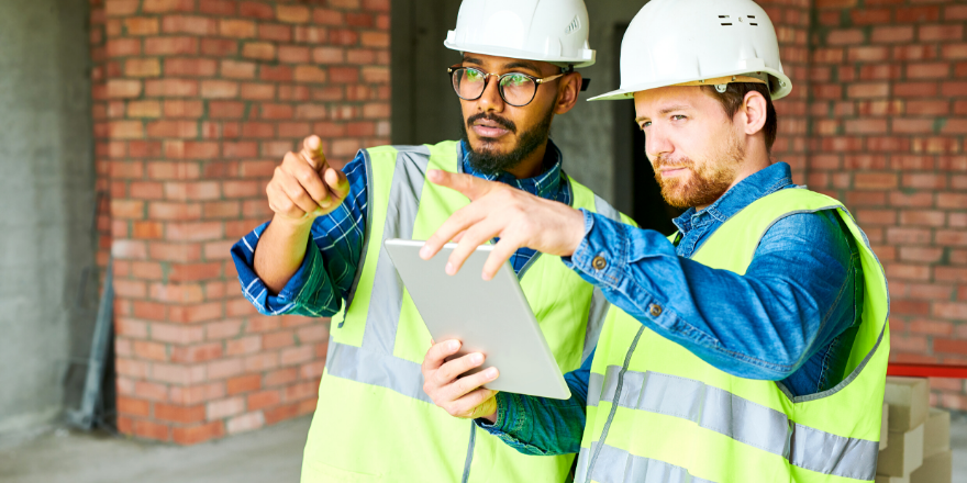 Two construction workers viewing a tablet and pointing in the distance.