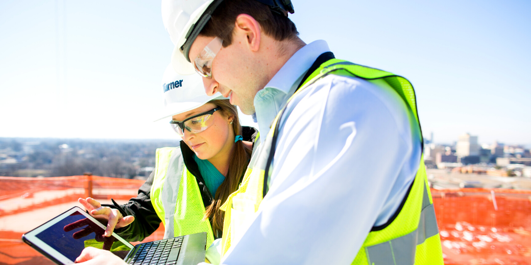 Two Turner Construction workers viewing a digital workforce management platform on site.