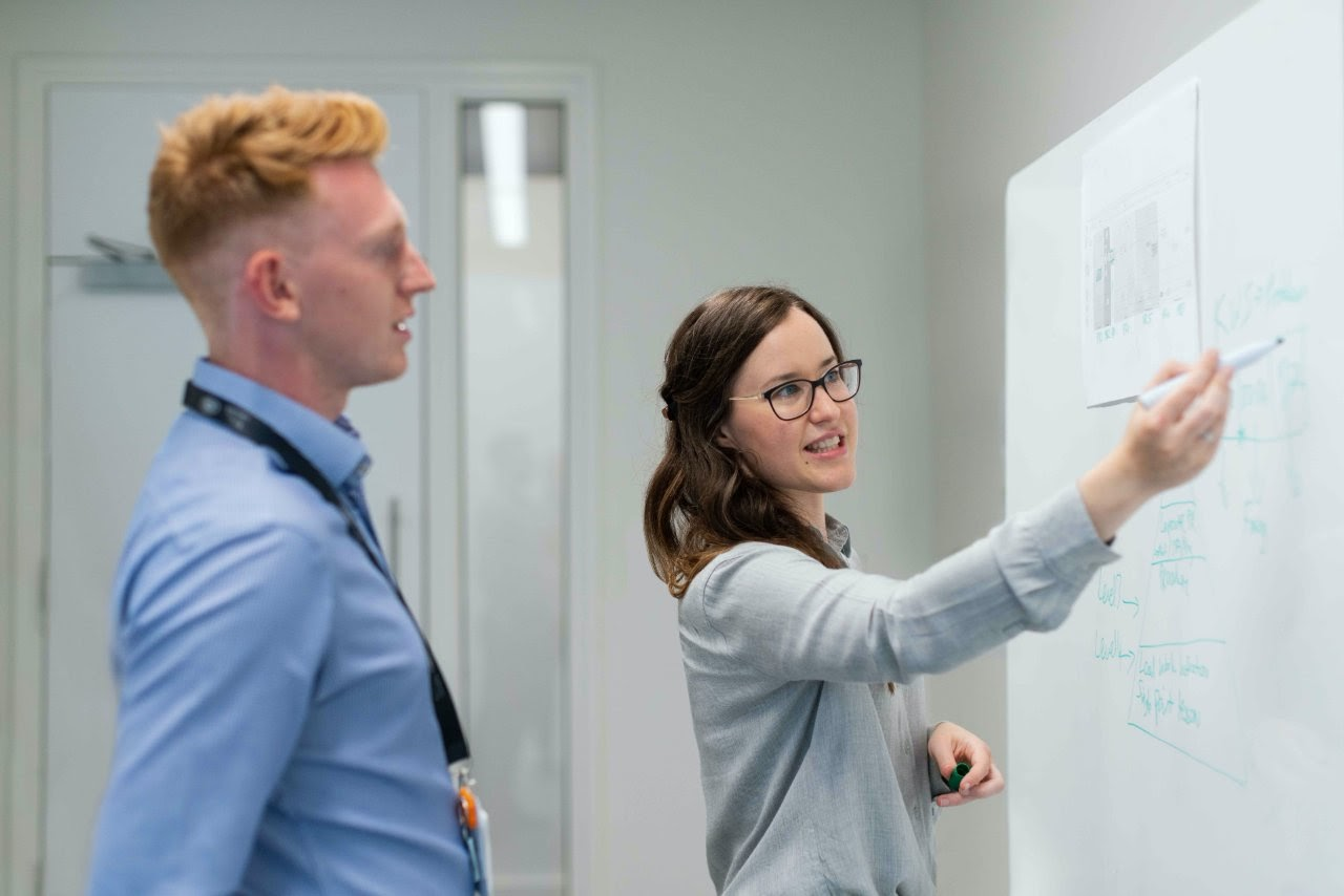 A woman draws a picture on a whiteboard to demonstrate an idea to a male coworker.