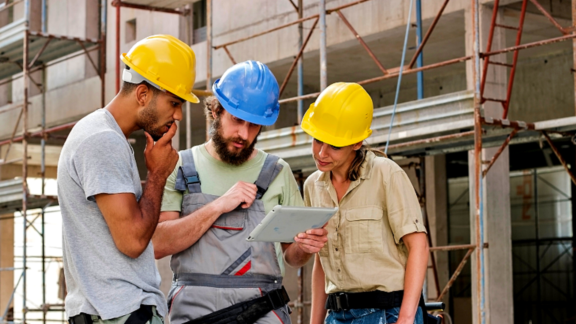 A trio of construction workers look at a tablet on a job site.