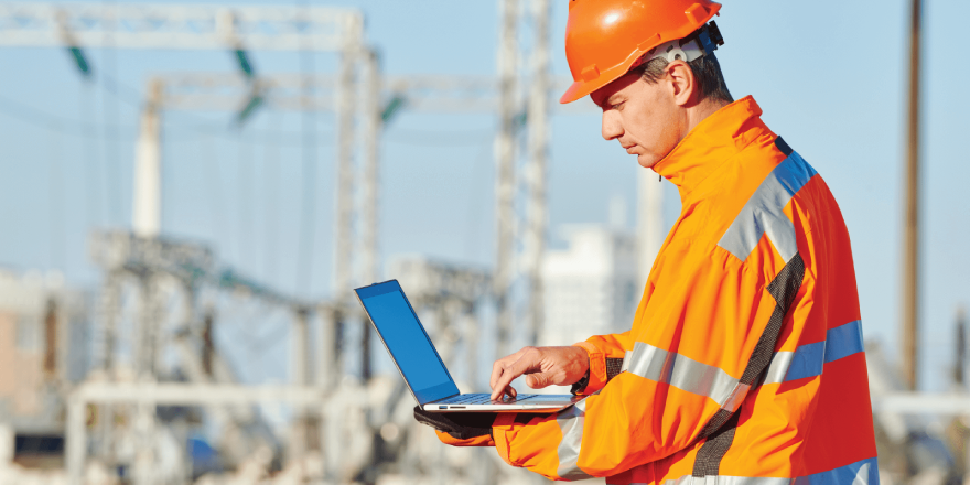 A construction worker in an orange jacket and hardhat typing on a laptop.