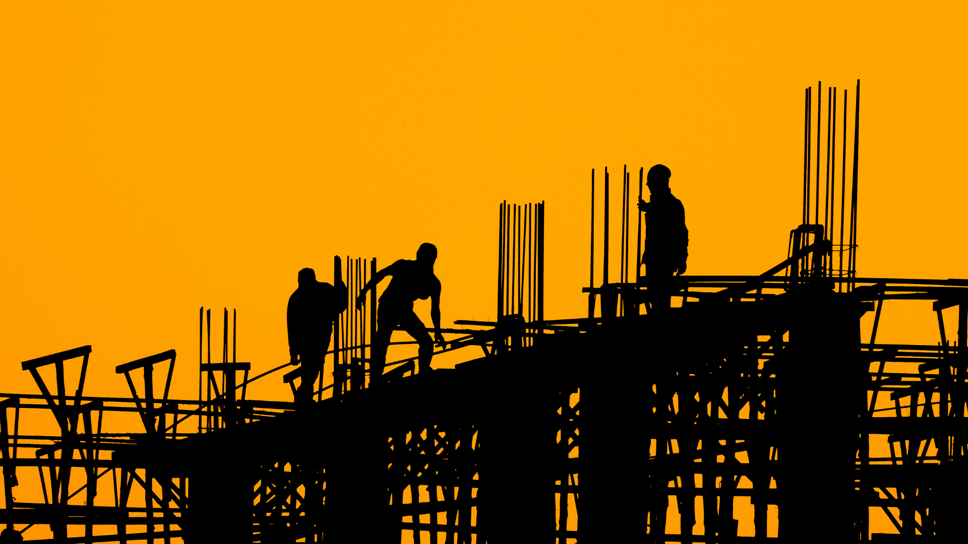 A pair of construction workers on a site at sunset.