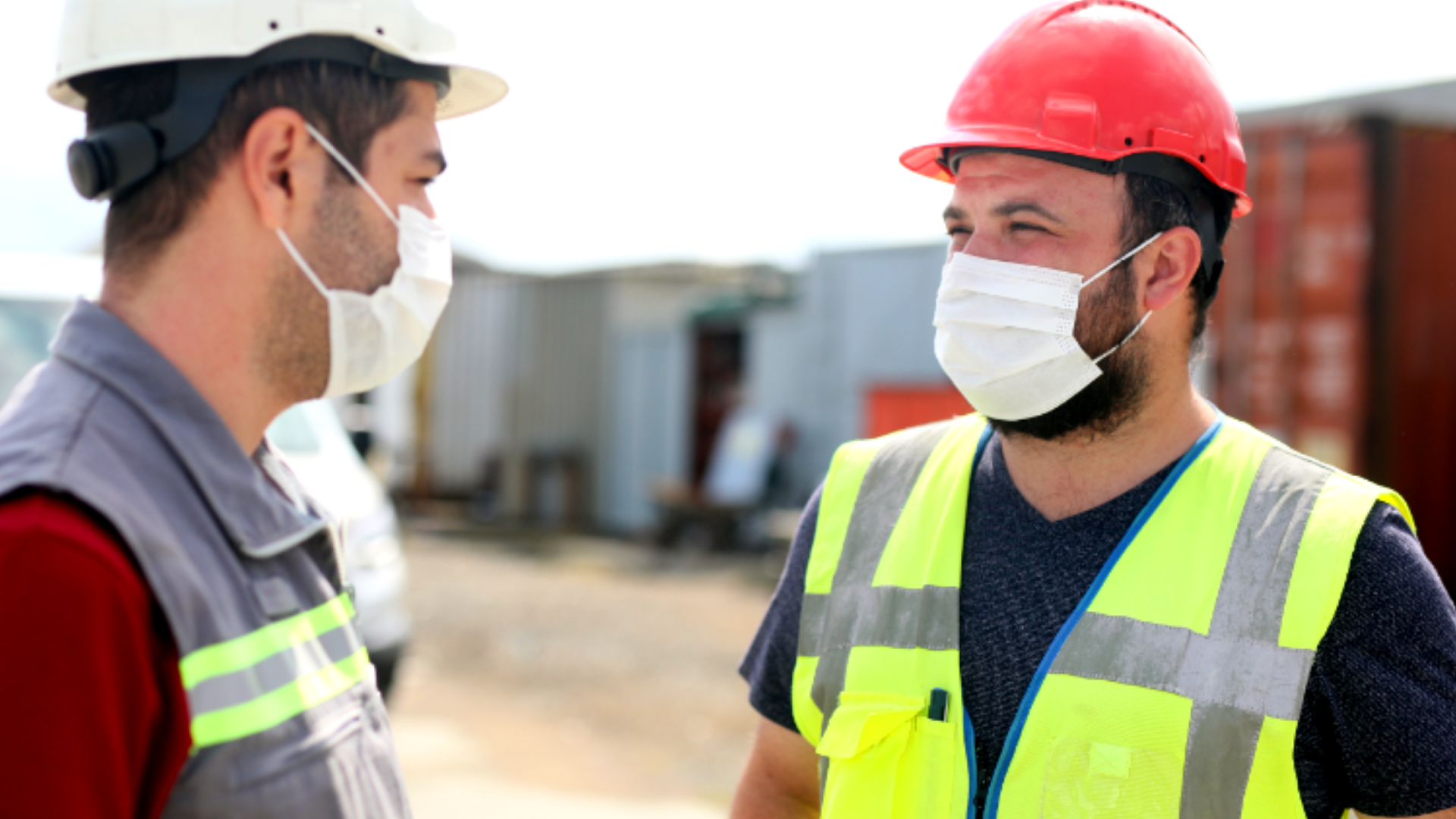 Two construction workers having a conversation while social distancing with masks on.