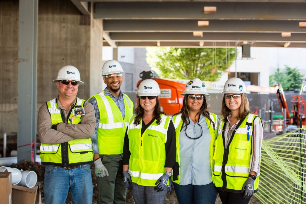 Five construction workers from Turner Construction standing in a line smiling.