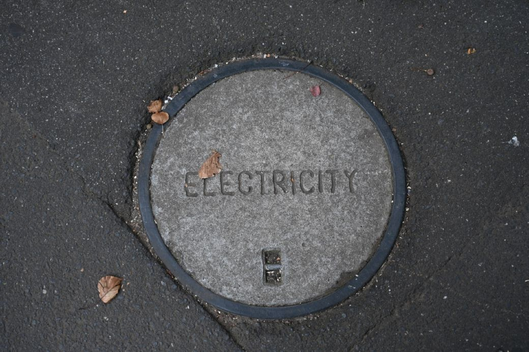 """A manhole cover with the word, """"electricity,"""" in the middle."""