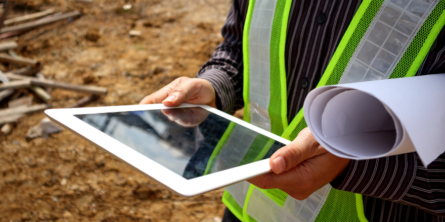 A construction worker holding a white tablet and blueprints