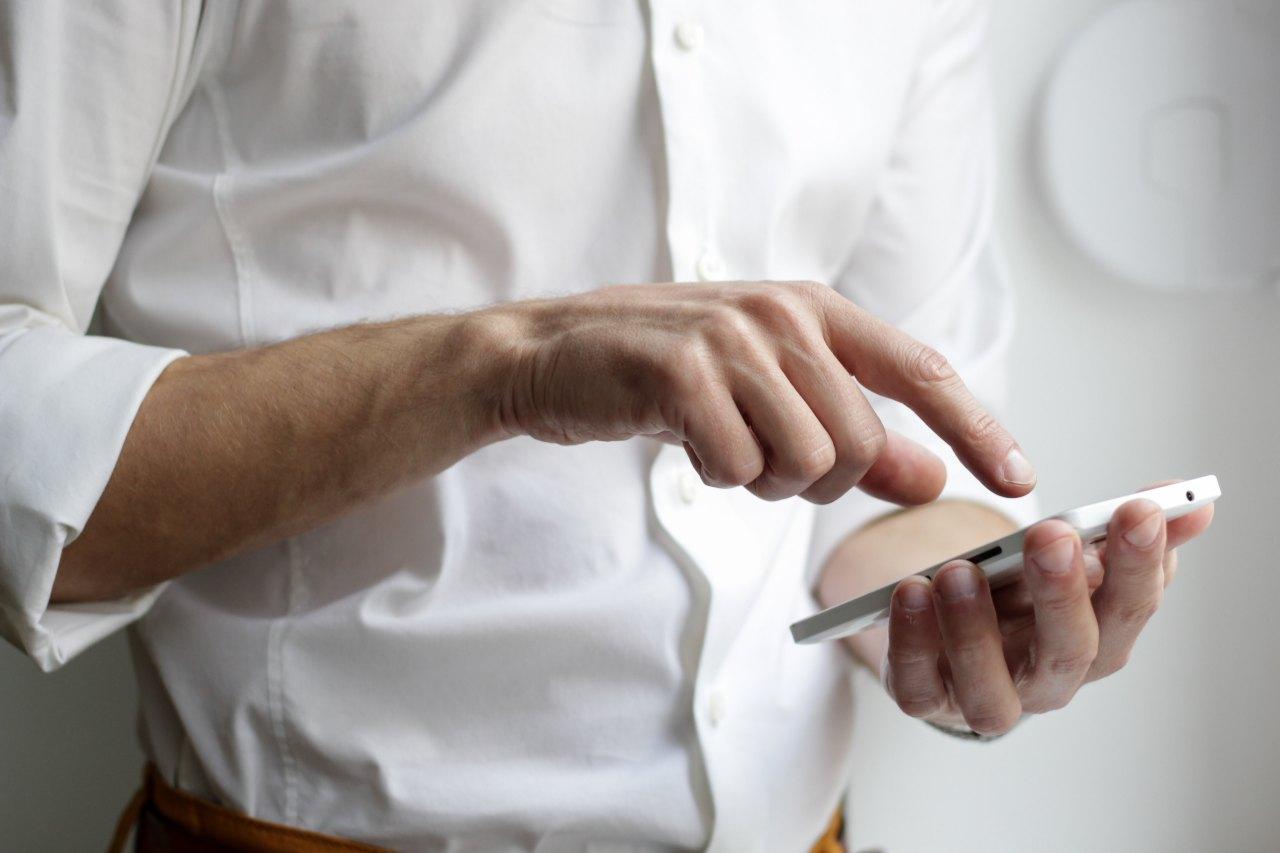 A man in an oxford shirt sends a text message.
