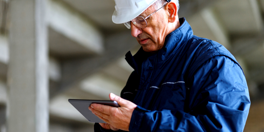 A male construction worker looking at his tablet.