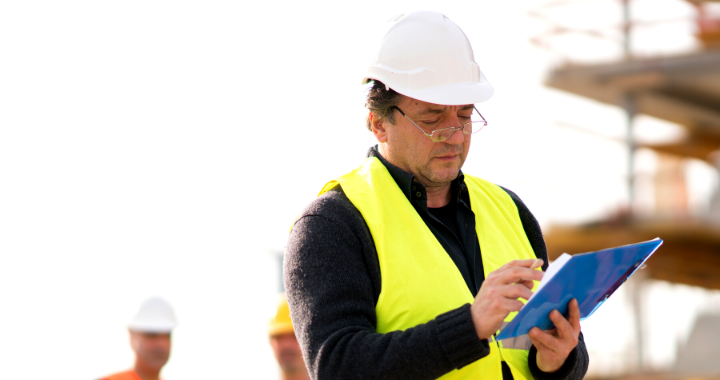 A construction worker in a yellow vest working on his tablet.
