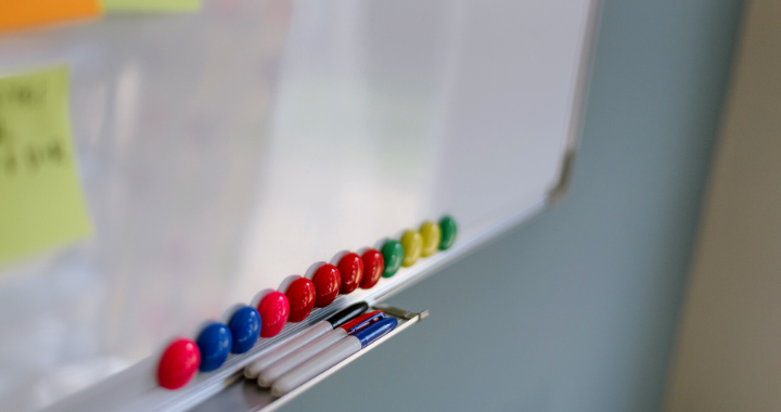 The bottom of a whiteboard with writing, sticky notes, magnets and dry erase markers.