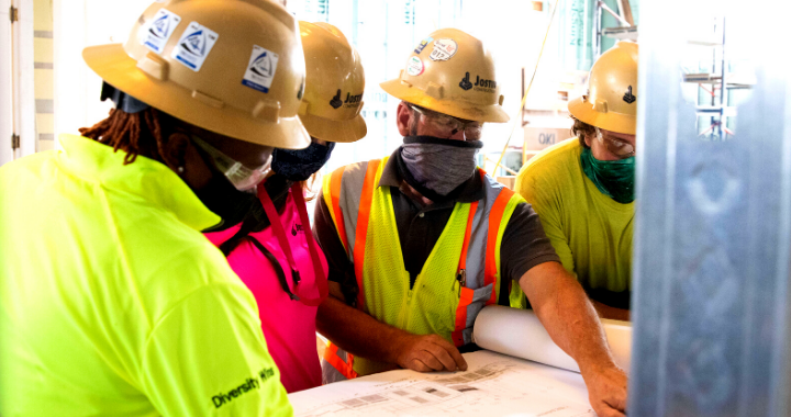 Three Jostin Construction workers looking at blue prints.
