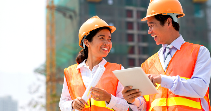 A male and female construction worker laughing and pointing at a tablet.