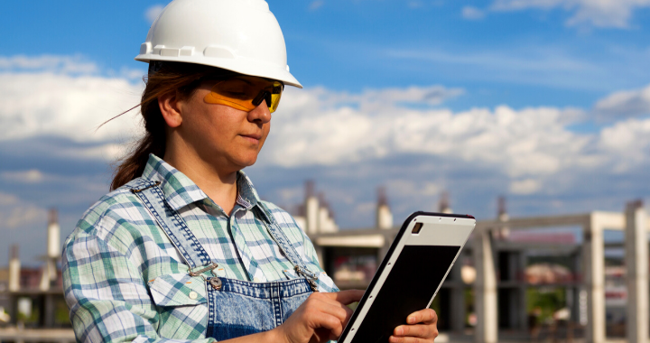 A woman construction worker on a tablet looking out in the distance.