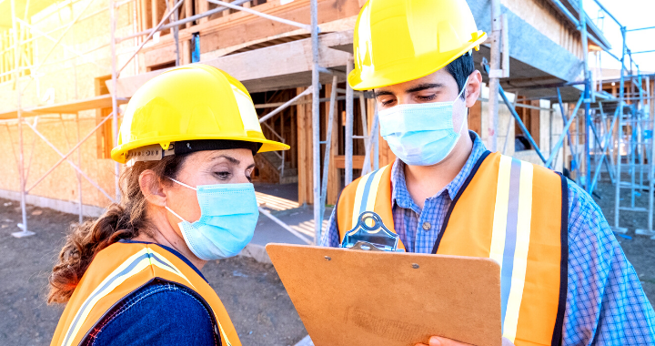 A construction worker writing with a pen on a clipboard and another construction worker looking over his shoulder.