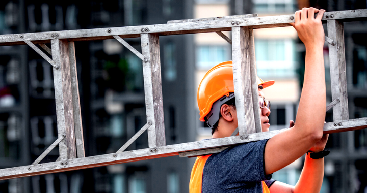 A male construction worker carrying a ladder.