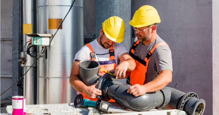 Two plumbing-specific construction workers attaching two pipes.