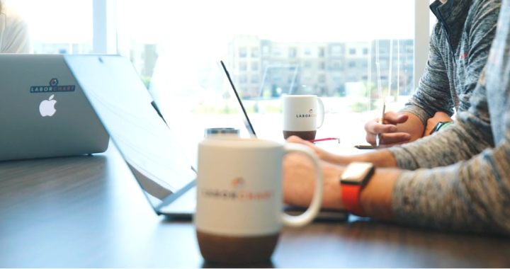 A LaborChart coffee mug with LaborChart employee's laptops and arms in the background.
