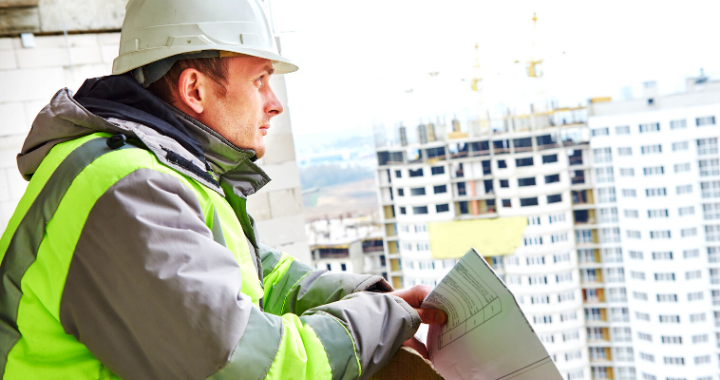 A construction worker looking off the balcony of a building holding sheets of paper.