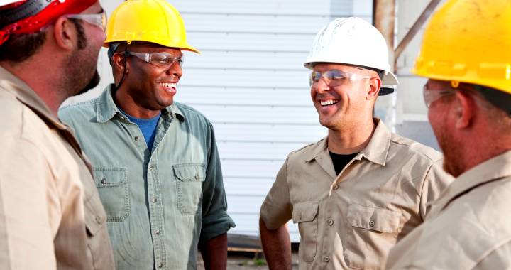 Four construction workers talking and laughing in a circle.