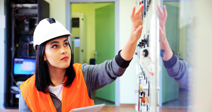 A woman construction worker moving electrical switches.