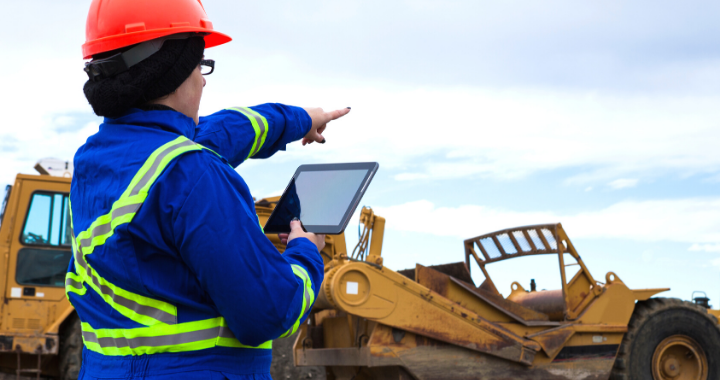 A construction worker managing her workforce in the field from the cloud.