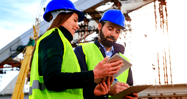 Male and female construction workers with blue hard hats managing their workforce at a construction site on a tablet.