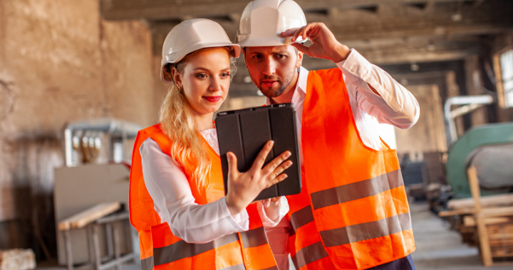 A female construction worker looking at a tablet with happiness, and a male construction worker looking at the tablet shocked.