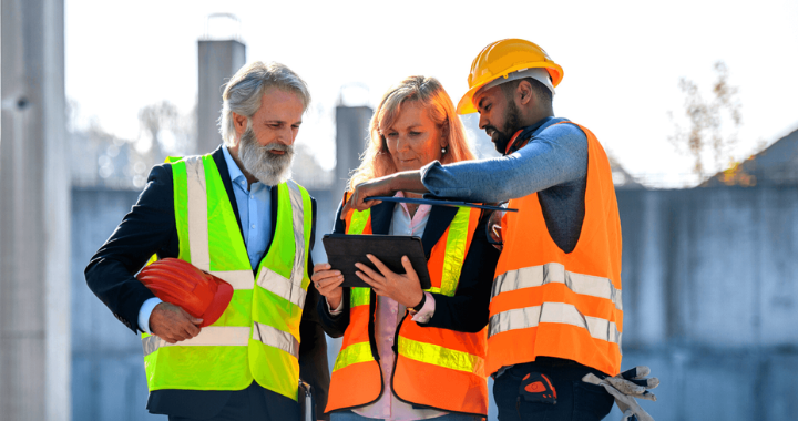 Two male and one female construction workers in safety gear observing a workforce management platform on the iPad.