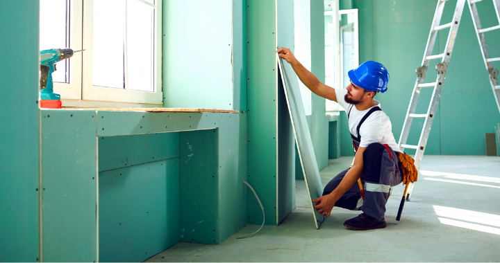 A construction worker constructing walls and ceilings structures in a building.