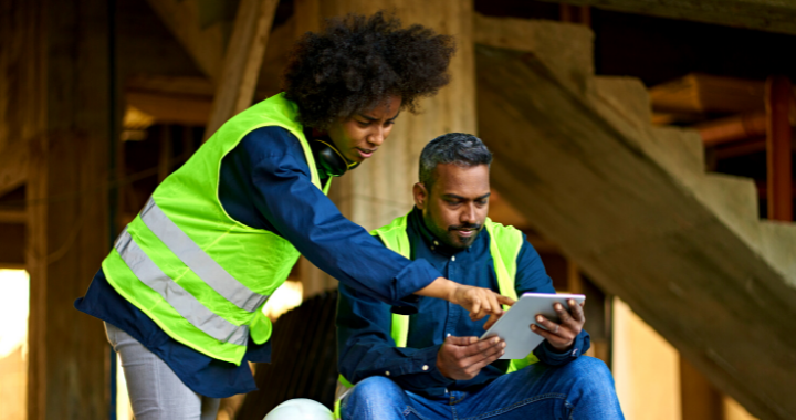 A male and female construction worker managing their workforce on a tablet.