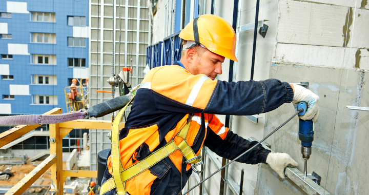 Construction worker on the side of a building drilling into a metal pole.