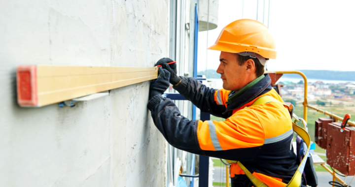 Male construction worker marking the level point on a building with a level.