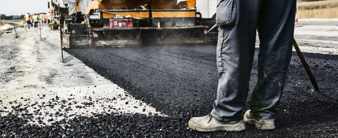Man's legs on newly laid asphalt during road construction.