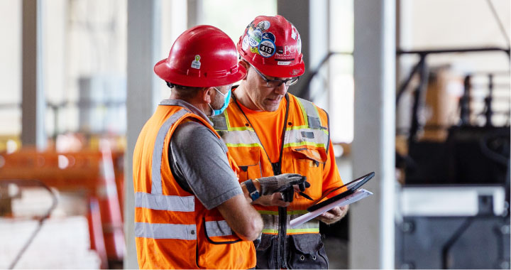 Two construction workers in red hard hats consult a tablet to manage their workforce on a jobsite.