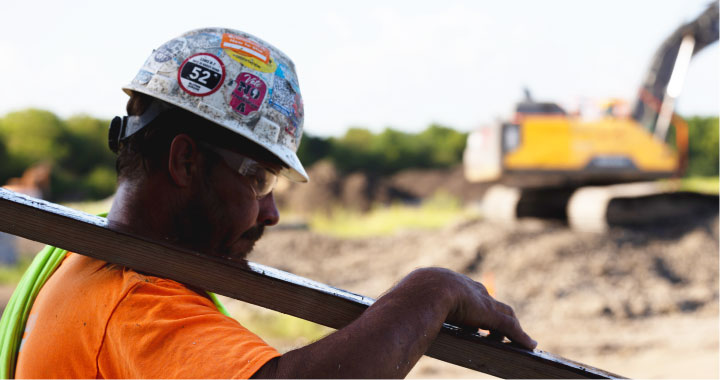 Construction worker wearing a hardhat covered in stickers carries a beam on a jobsite.