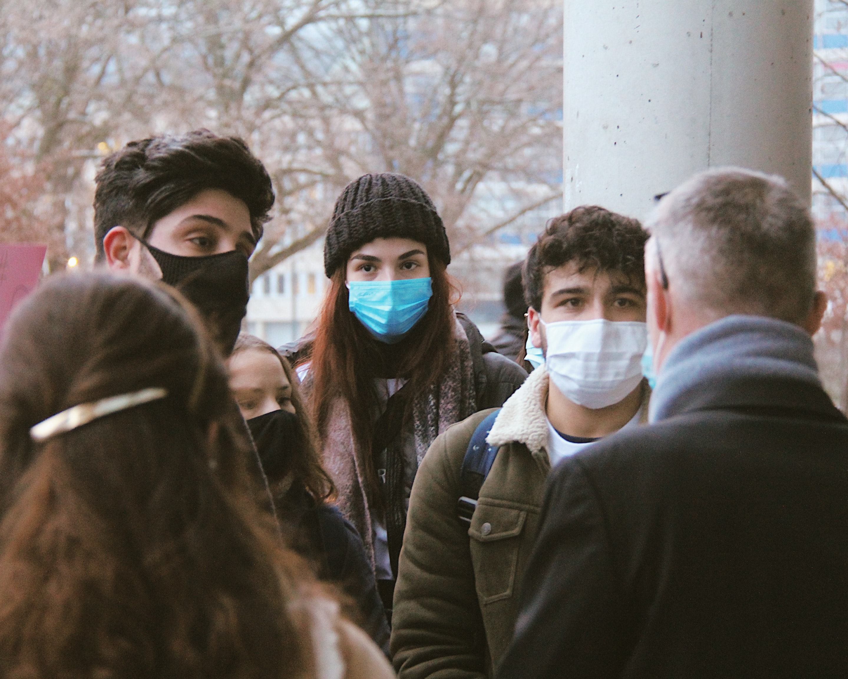 Students standing outside in winter coats and medical face masks
