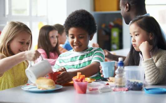 Young children eating a school lunch together.