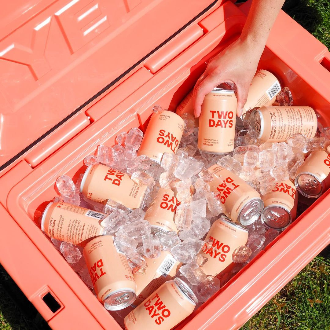 A pink YETI cooler filled with Two Days Drinks vodka sodas and ice. A hand is taking one of the cans out of the cooler.