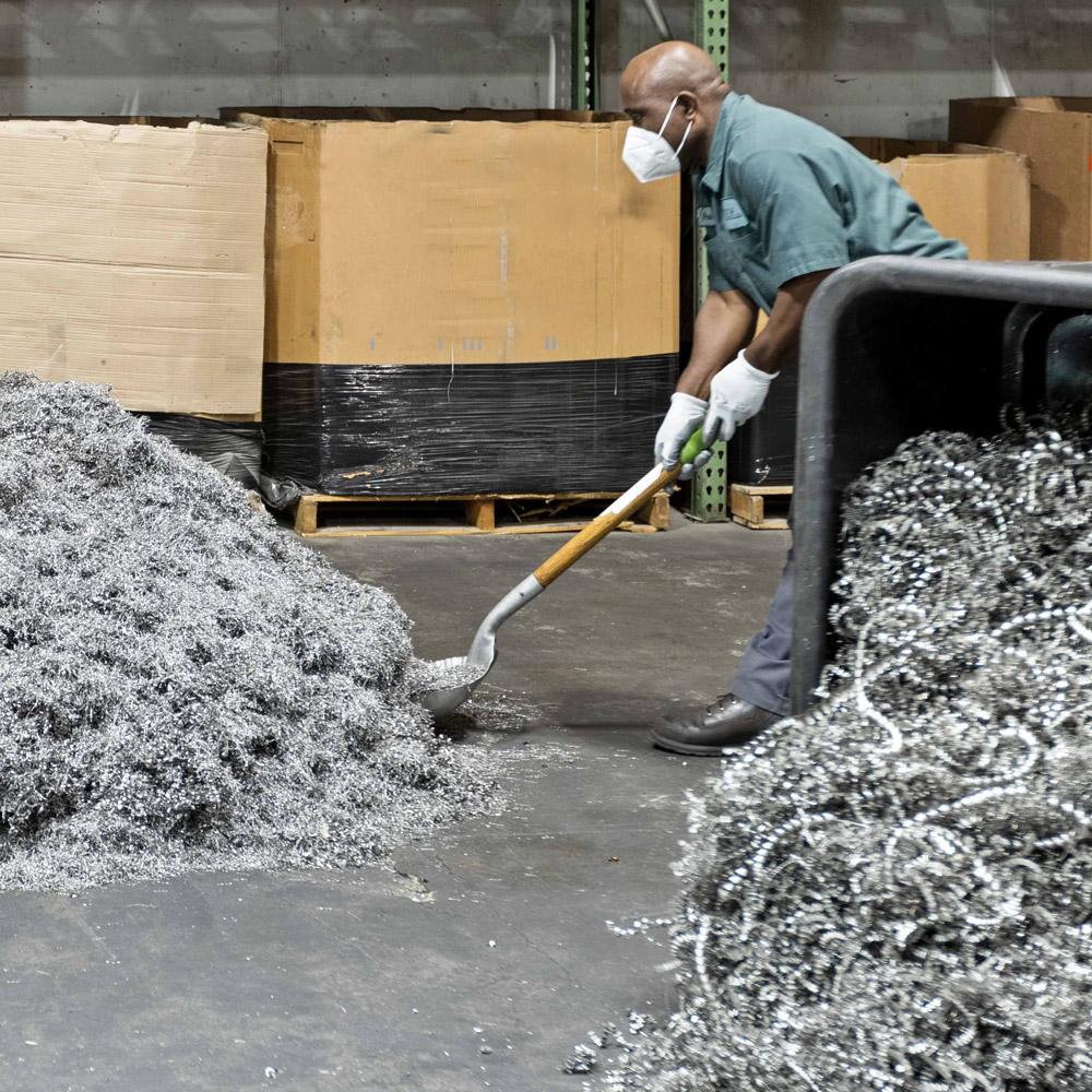 Worker shoveling scrap metal
