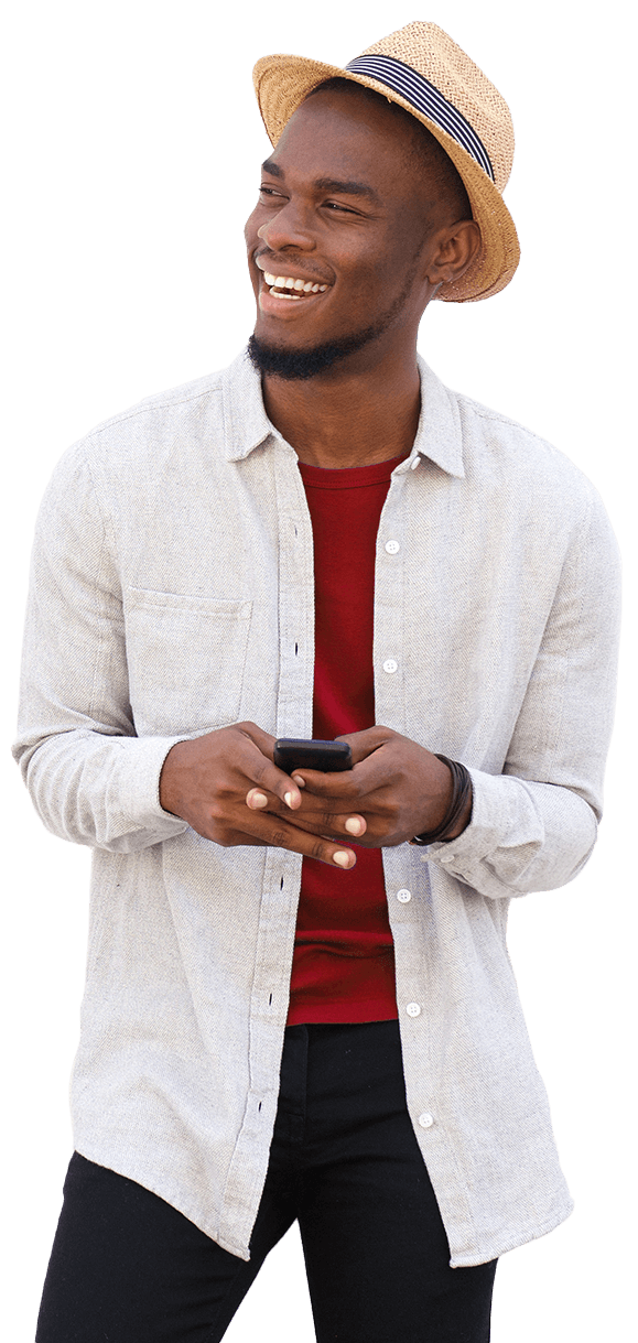 Happy young man in a straw hat and white shirt holding a mobile phone.