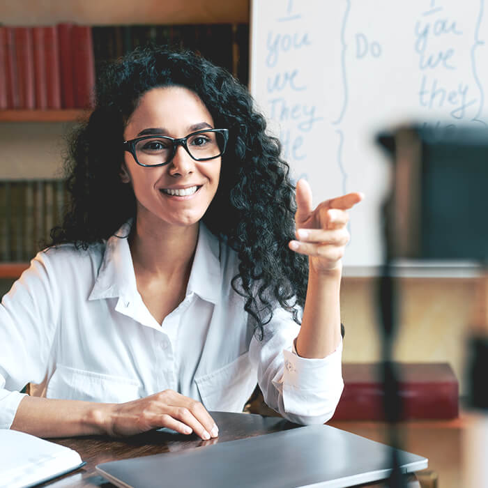 Happy young woman sitting at a desk wearing a white shirt with long curly black hair. She's pointing with her left hand and speaking into a camera.