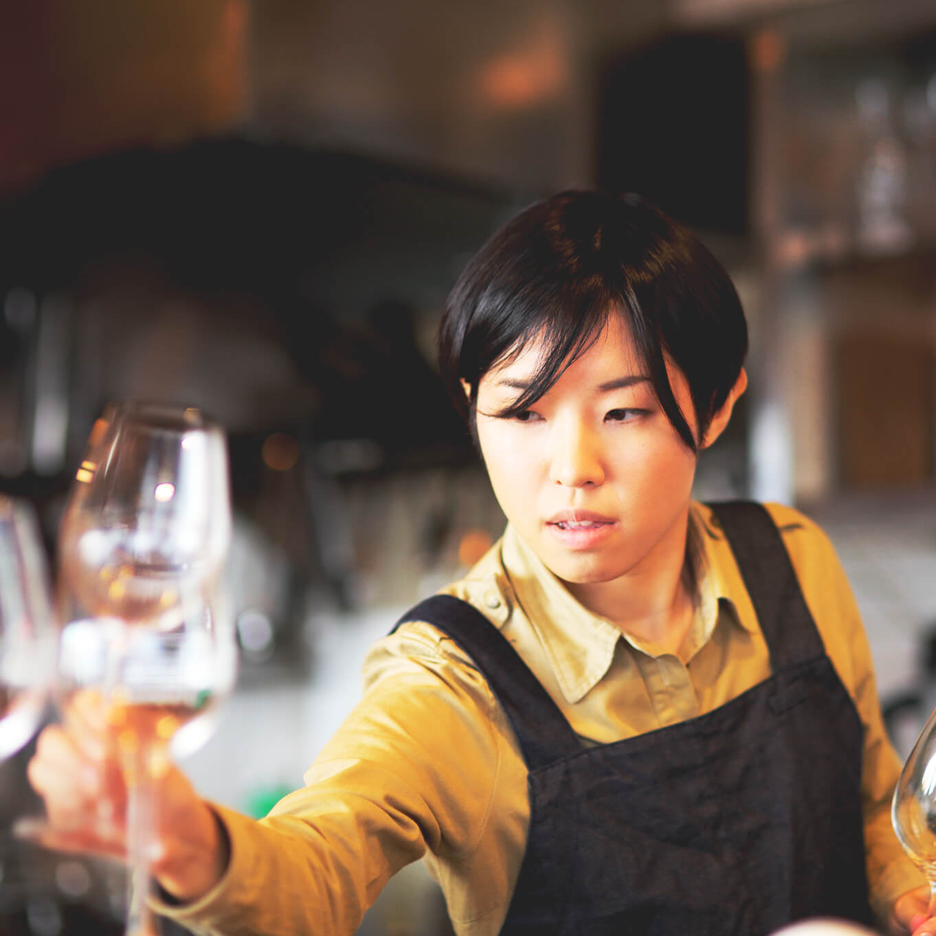 Young woman with black hair wearing a yellow shirt and black apron carefully placing wine glasses on a table.