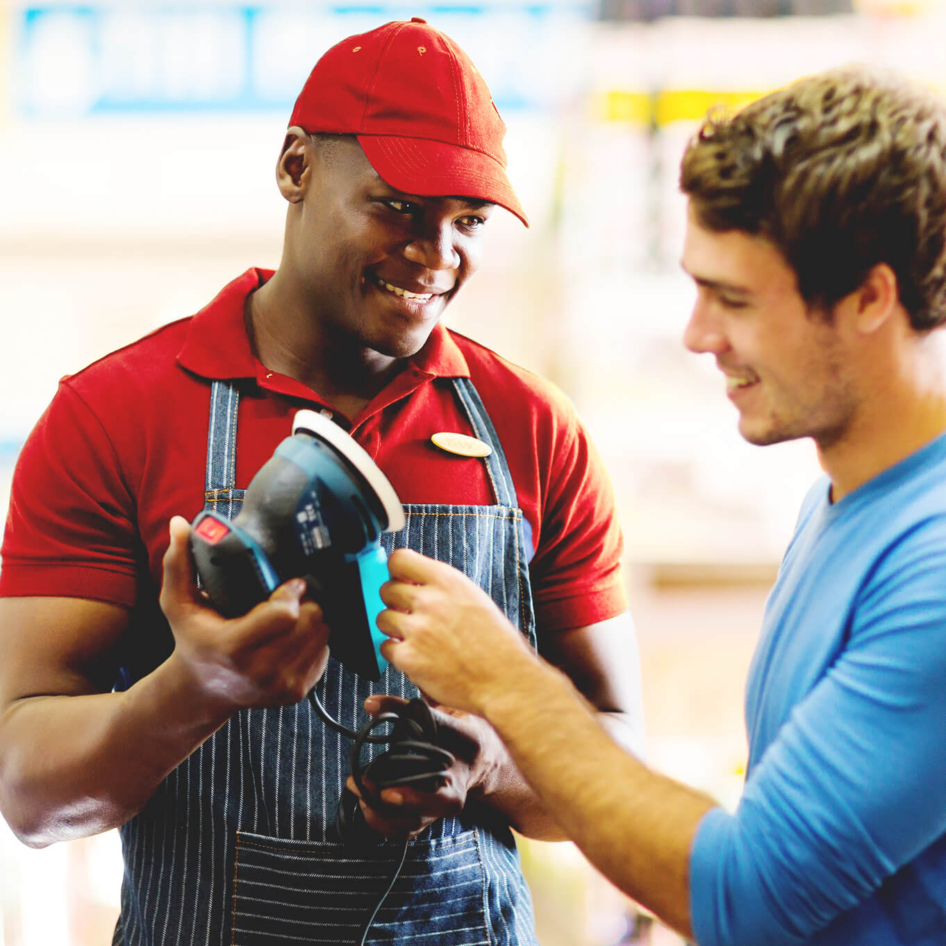 Smiling retail worker in a red hat, red shirt and blue & white striped apron. He helps a customer in a blue shirt chose a power tool.