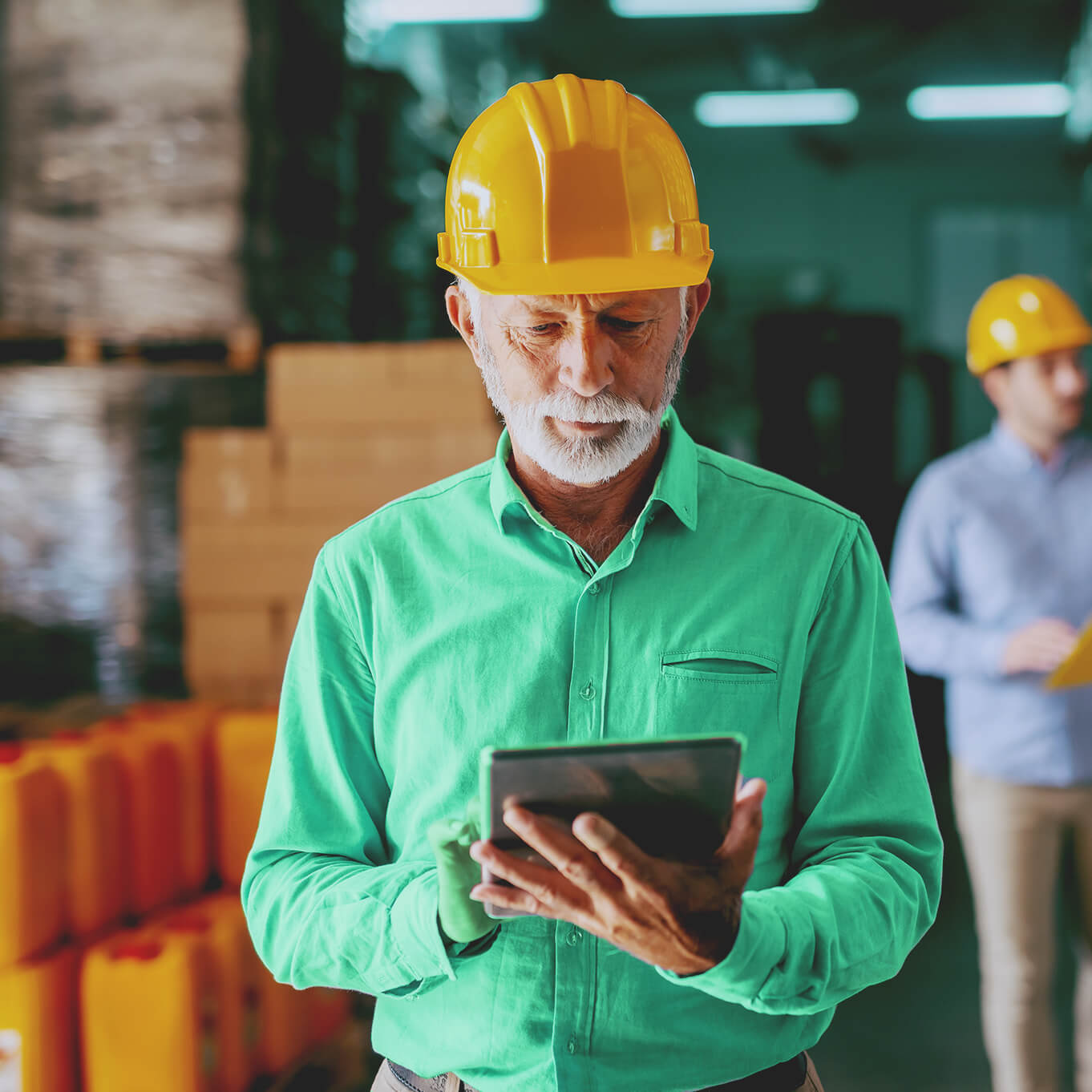 Elderly construction worker with a white beard wearing a yellow hard hat and light green shirt. He looks over the tablet he holds with a look of concentration on his face.